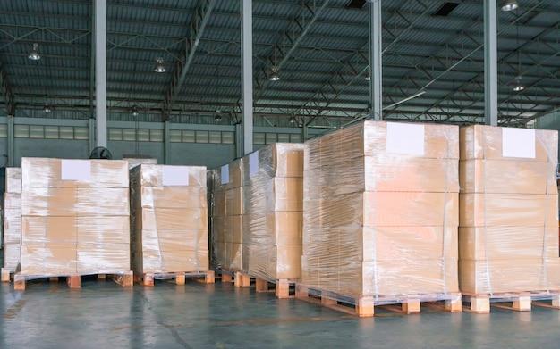 Stapel von verpackungsboxen, die plastik auf paletten im lager einwickeln