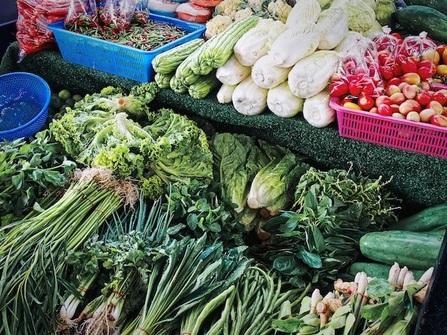Stapel von verschiedenen arten von frischem grünem kräutergemüse zum verkauf am marktstand