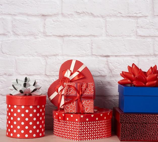 Stapel von verschiedenen kisten mit geschenken auf weißer backsteinmauer