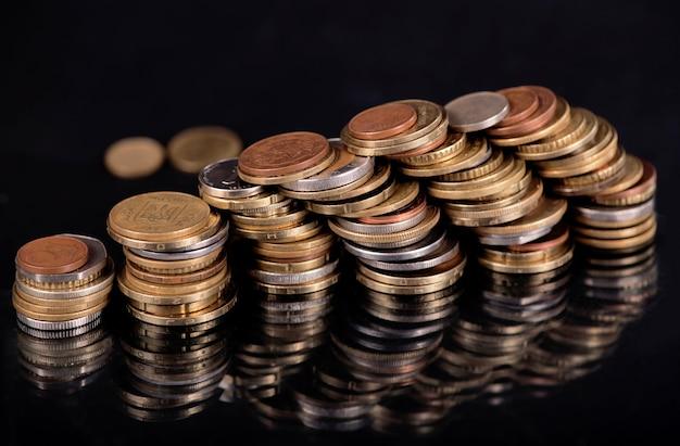 Stapel von verschiedenen landmünzen auf schwarzem hintergrund.