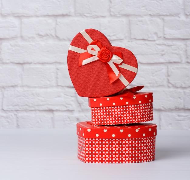 Stapel von verschiedenen roten kästen mit geschenken auf weißem hintergrund, festlicher hintergrund