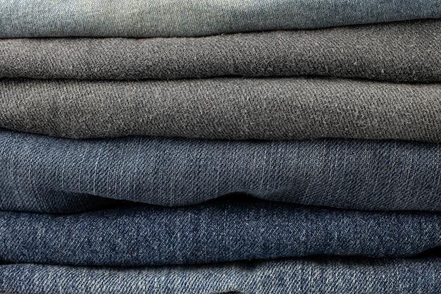 Stapel von verschiedenen schattierungen von blue jeanshosen auf weißem hintergrund