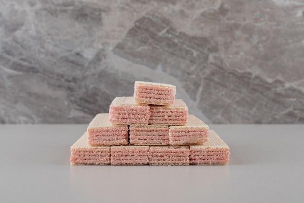 Stapel von waffeln mit erdbeercremefüllung auf marmorhintergrund.