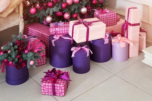 Stapel von weihnachtsgeschenken unter einem geschmückten weihnachtsbaum