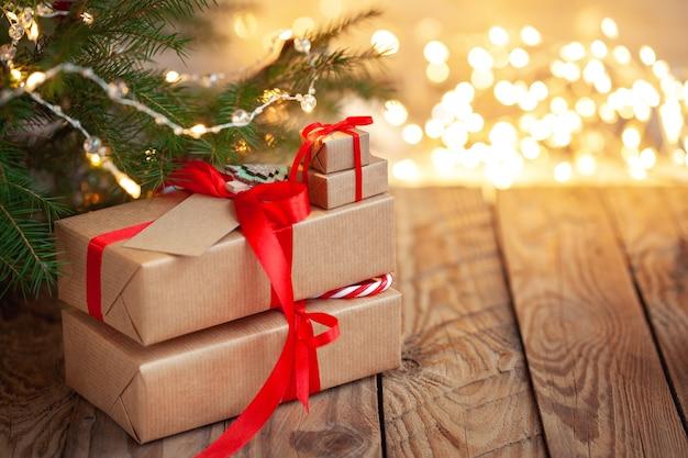 Stapel von weihnachtsgeschenken unter einem weihnachtsbaum mit defokussierten lichtern.