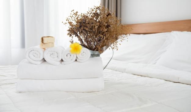 Stapel von weißen handtüchern, seifen, kerze und getrockneten blumen gesetzt