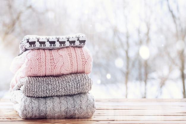 Stapel von wollstrickkleidung auf hölzernem tisch auf winterhintergrund