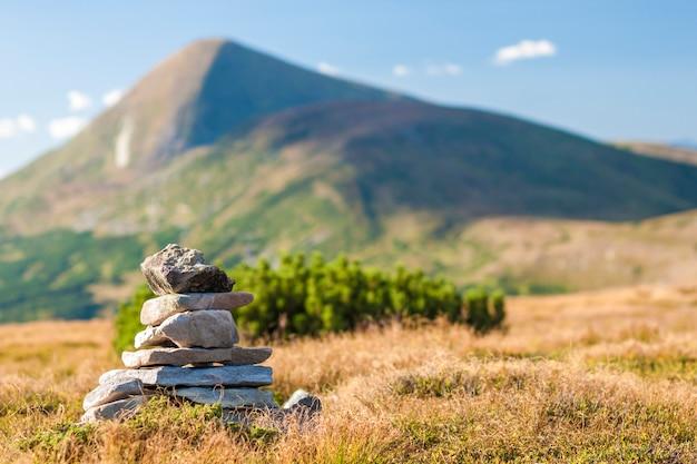 Stapel von zen-steinen mit blick auf die spitze des berges. konzept von gleichgewicht und harmonie.