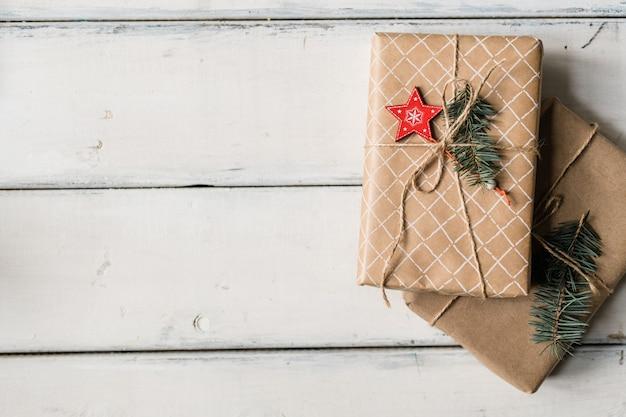 Stapel von zwei eingewickelten geschenkboxen, die mit fäden auf weißem tisch gebunden werden, der als weihnachtshintergrund verwendet werden kann