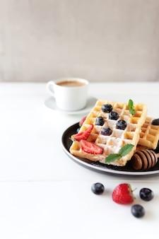 Stapel waffeln auf einem teller auf dem weißen tisch mit blaubeere, gehackten erdbeeren und minzblättern und weißer tasse und teller kaffee. foto in hoher qualität