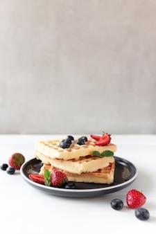 Stapel waffeln auf einem teller auf dem weißen tisch mit blaubeeren, gehackten erdbeeren und minzblättern, grauer hintergrund. foto in hoher qualität
