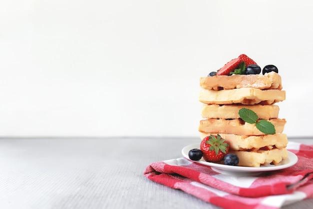 Stapel waffeln auf einem weißen teller auf dem handtuch und dem tisch mit blaubeeren, gehackten erdbeeren und minzblättern. foto in hoher qualität