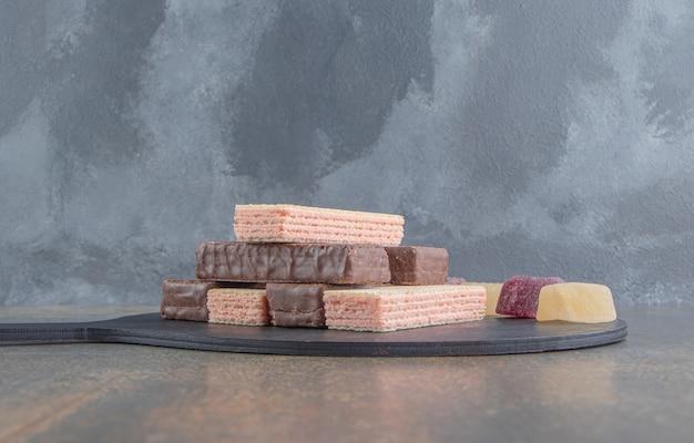 Stapel waffeln mit marmeladen auf kleinem brett auf holztisch