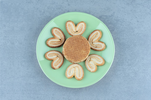Stapel waffeln und kekse auf grüner platte.