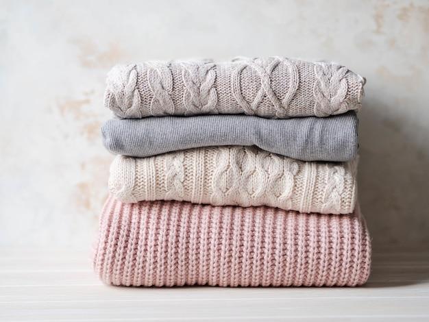 Stapel warme gestrickte pastellfarben der woolen strickjacken gegen beige strukturierte wand. kopieren sie platz