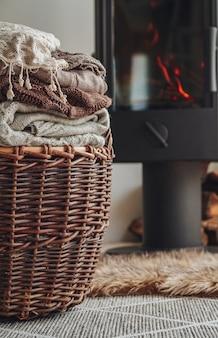 Stapel warmer kleidung in einem weidenkorb und einem eisernen kamin