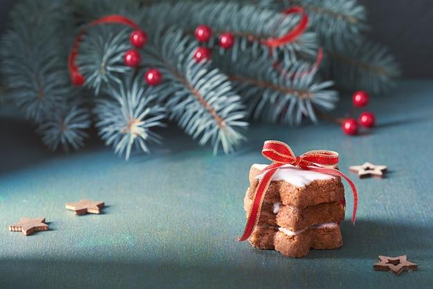 Stapel weihnachtssternplätzchen band herauf rotes band des stärkes auf grünem und rotem festlichem hintergrund