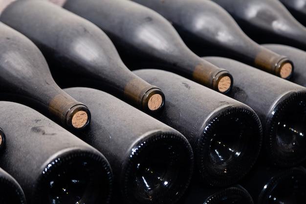 Stapel weinflaschen, die flach in gestelle im alten weinkeller oder in der höhle legen