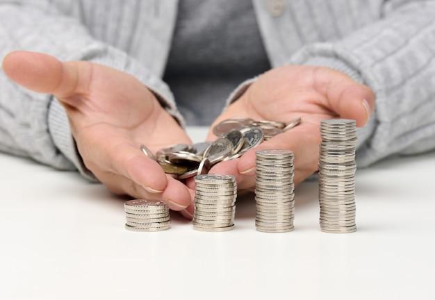 Stapel weiße münzen und weibliche hände halten einen haufen münzen. armut, budgetplanung. zuschuss und geringes gehalt