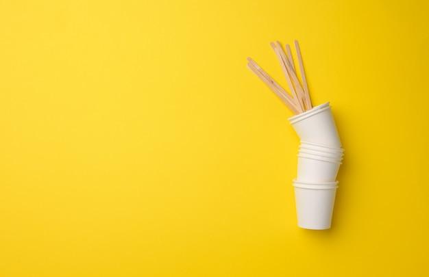 Stapel weiße pappbecher auf gelbem grund. konzept der kunststoffablehnung, null abfall, kopienraum