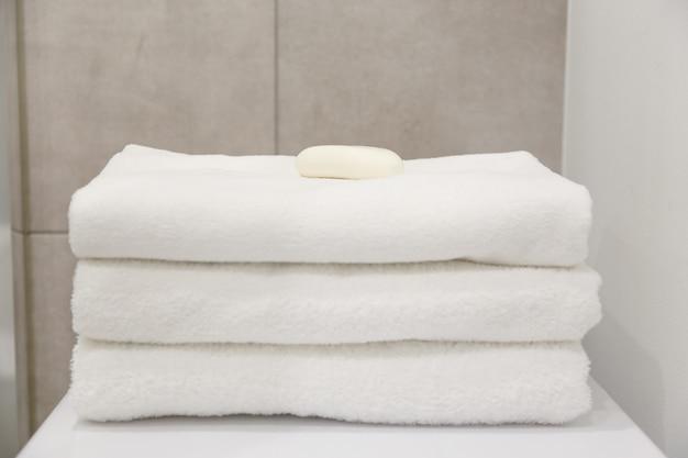 Stapel weiße saubere tücher auf tabelle im badezimmer