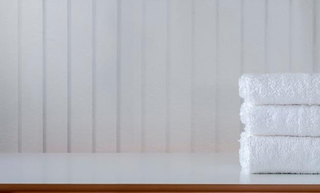 Stapel weißer handtücher auf dem tisch.