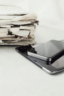 Stapel zeitungen mit digitalem tablet und smartphone