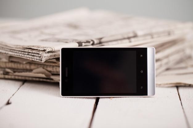 Stapel zeitungen mit smartphone drauf