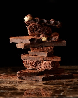 Stapeln sie dunkle schokolade isoliert auf einer dunklen marmoroberfläche