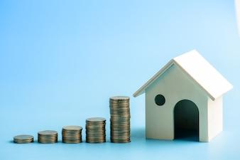 Stapeln von Dollar-Münzen mit einem Haus-model.save und Investitionen für kaufen Hauskonzept. Pastellton.