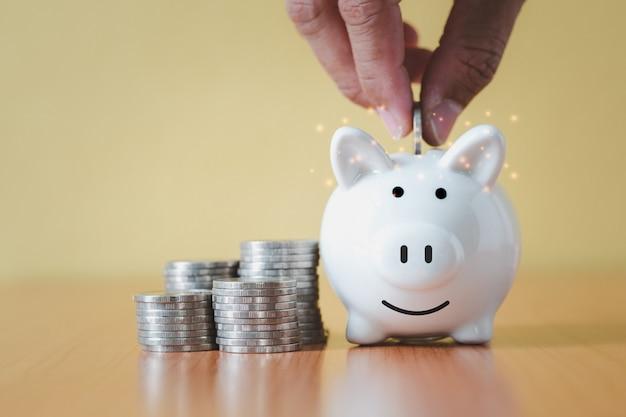 Stapeln von münzen stapeln und hand münze in weißes sparschwein legen, um mit geld zu sparen und zu planen, wachsen, geld für die pensionskasse und das zukunftsplan-konzept sparen.