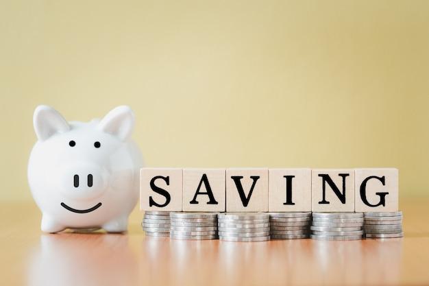 Stapeln von münzen stapeln und weißes sparschwein und holzkiste mit textwortsparen für planungsschritt bis zum wachsen, geld sparen für pensionskasse und das zukunftsplankonzept.