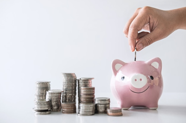 Stapelstapel und hand, die münze in sparschwein für die planung stecken, steigern zum wachsen
