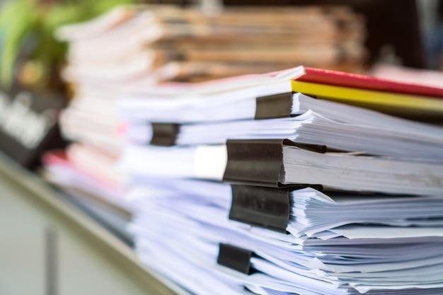 Stapelt unvollendete dokumente, meldet dateien mit überarbeiteter papierecke auf dem schreibtisch der lehrerschule an der universität von thailand. stapel unordentlicher papierkram-bewertungs-rechtsordner am arbeitsplatzkonzept