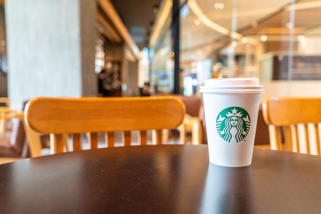 Starbucks-heißgetränkekaffee mit halter auf dem tisch