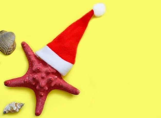 Starfish in einem weihnachtshut auf gelb.