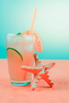 Starfish nahe dem pampelmusencocktail auf korallenrotem schreibtisch gegen knickentenhintergrund