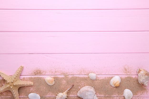 Starfish und muscheln mit sand auf rosa hölzernem. sommer-konzept