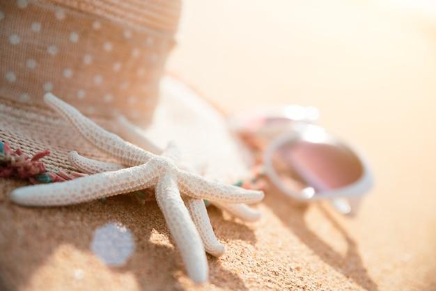 Starfish- und strandzubehör auf hintergrund des sandigen strandes für sommerkonzept.