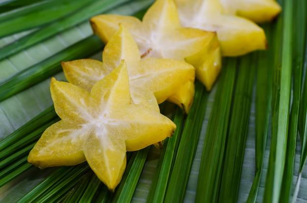 Starfruit, carambola auf grünem blatt