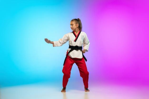 Stark. karate, taekwondo-mädchen mit schwarzem gürtel einzeln auf farbverlaufshintergrund im neonlicht. kleines kaukasisches modell, sportkindertraining in bewegung und aktion. sport, bewegung, kindheitskonzept.