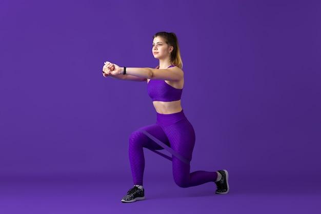 Stark. schöne junge sportlerin üben, einfarbiges lila porträt. sportliches modell mit kaukasischer passform mit gummizügen. bodybuilding, gesunder lebensstil, schönheits- und aktionskonzept.