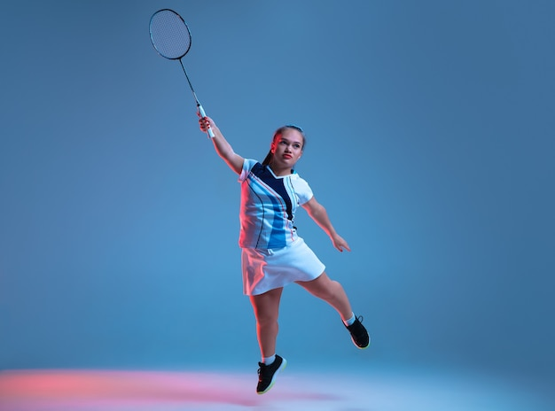Stark. schöne zwergfrau, die im badminton übt, lokalisiert auf blauem hintergrund im neonlicht. lebensstil inklusiver menschen, vielfalt und gleichberechtigung. sport, aktivität und bewegung. exemplar.