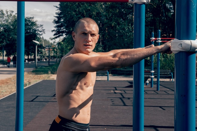 Stark trainierter mann athlet posiert auf dem sportplatz muskulöser starker körper