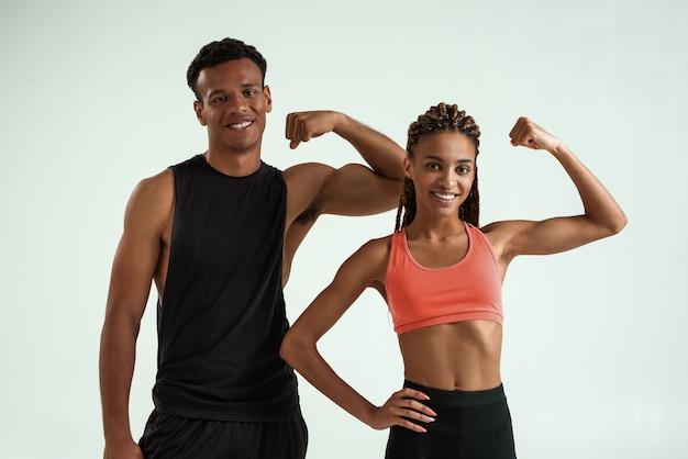Stark und gesund. junges lächelndes afrikanisches paar in sportkleidung, das muskeln zeigt und die kamera mit einem lächeln betrachtet, während es vor grauem hintergrund steht. sportkonzept. gemeinsam trainieren