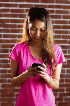 Starke asiatische frau, die smartphone auf backsteinmauer verwendet
