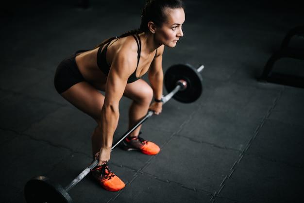 Starke bodybuilderin mit perfektem fitnesskörper, die sich darauf vorbereitet, die schwere langhantel vom boden zu heben. konzept des gesunden lebensstils und des trainings in einem modernen dunklen fitnessstudio.