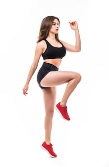 Starke brünette sexy frau in schwarzer sportbekleidung macht übungen für starke figur körper