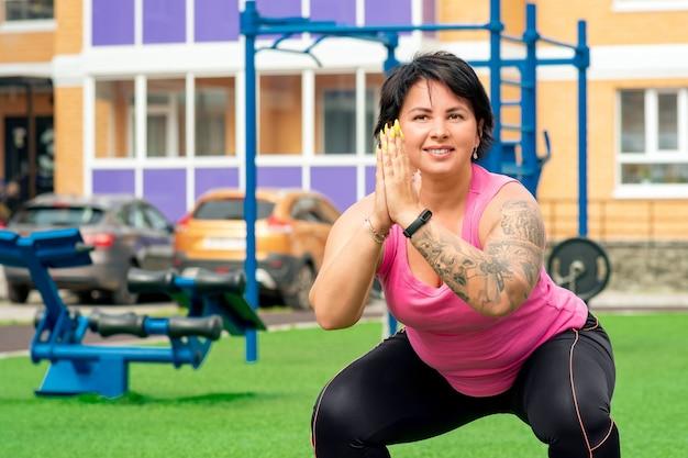 Starke, dicke frau, die kniebeugen auf einem sportplatz im innenhof eines stadthauses vor dem hintergrund von straßenübungsgeräten macht