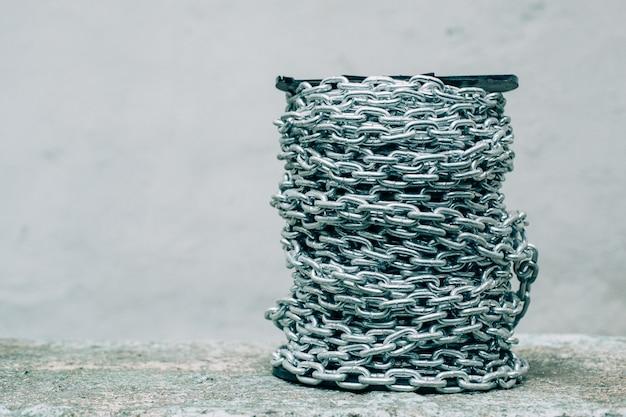 Starke eisen lange kette in einem strang auf dem konkreten hintergrund